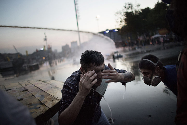 A protester reacts to tear gas fired by the riot police in Gezi Park